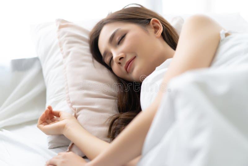 睡觉在她的床上和放松早晨的一名镇静年轻俏丽的亚裔妇女的特写镜头画象 享受晚安的夫人 免版税库存照片