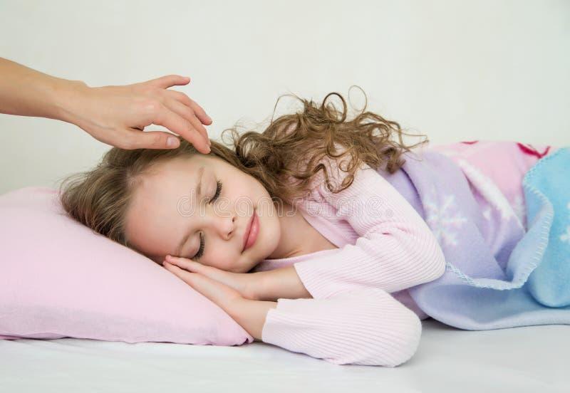 睡觉在她的床上的可爱的小女孩 库存图片
