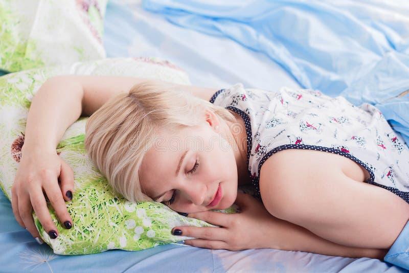睡觉在她的床上的年轻美丽的白肤金发的妇女早晨 免版税库存图片