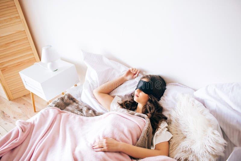 睡觉在她的床上的深色头发的美丽的年轻浅黑肤色的男人 在眼睛的黑睡觉面具 单独在卧室 ?? 免版税库存照片