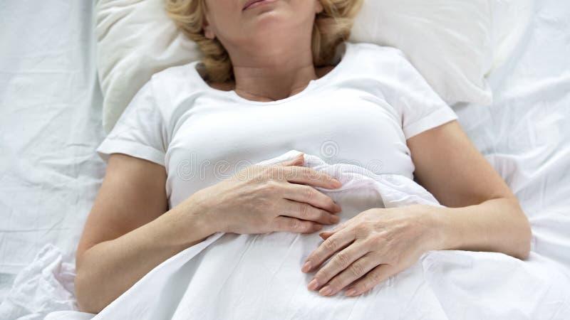睡觉在她的床上的资深妇女,顶视图起了皱纹手,退休,晚年 免版税库存图片