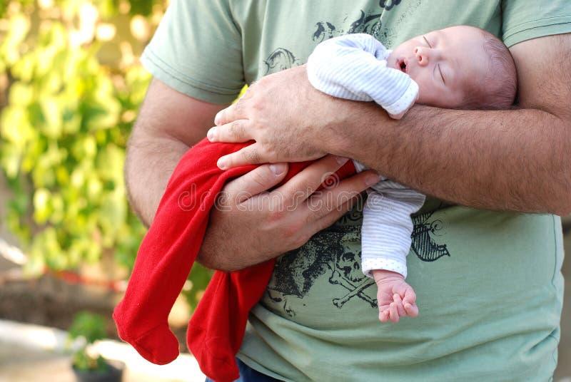 睡觉在她的父亲的新出生的女婴武装 免版税库存照片