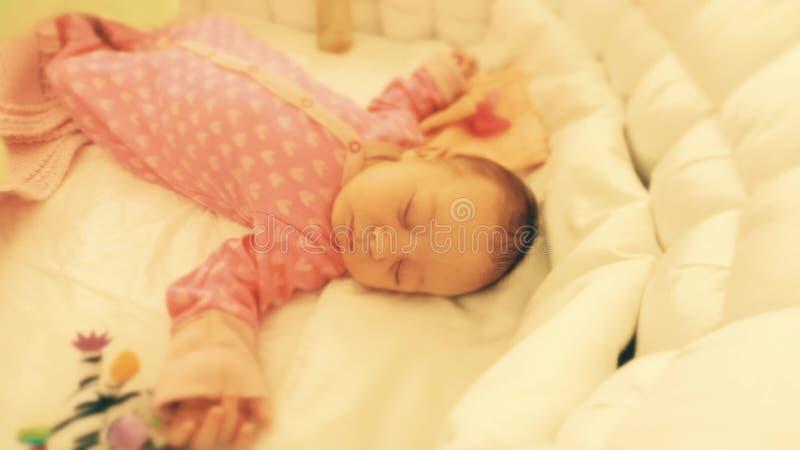 睡觉在她的轻便小床的逗人喜爱的新出生的女婴 库存照片