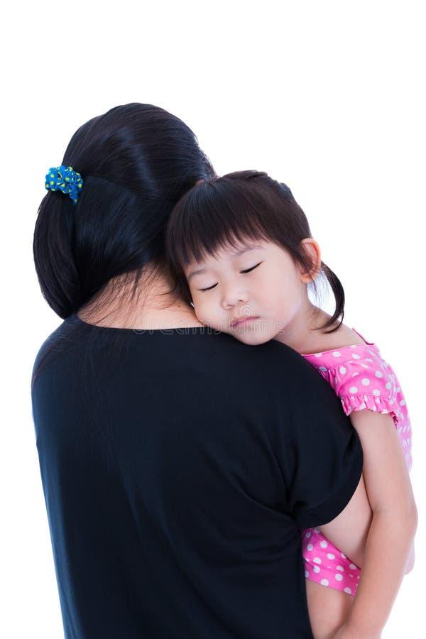 睡觉在妈妈的肩膀的可爱的亚裔女孩,在白色backgro 免版税库存照片