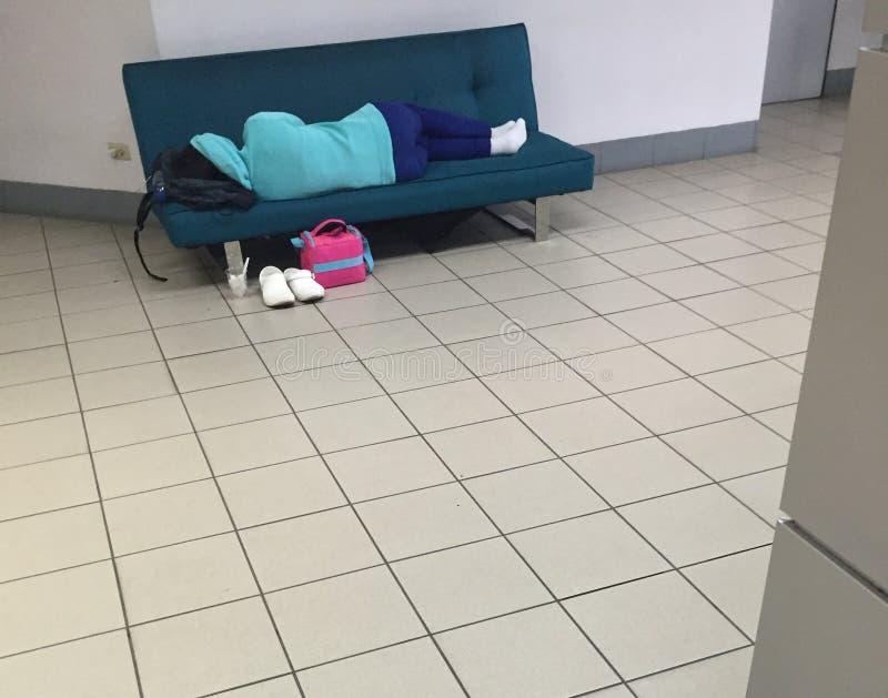 睡觉在学院长沙发的学生 库存照片