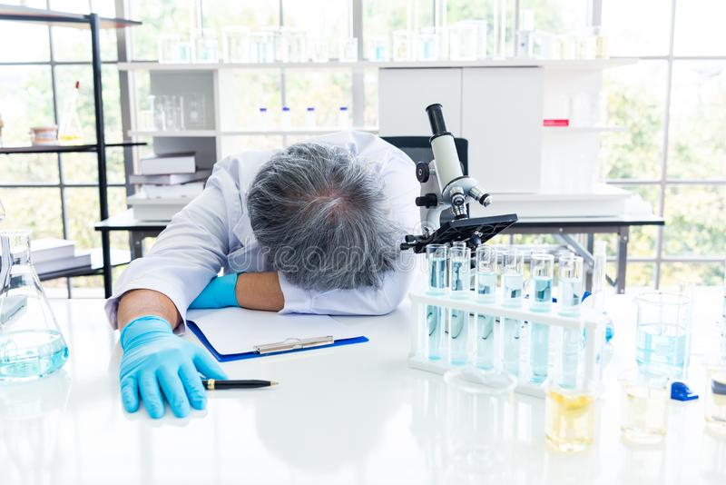 睡觉在实验室的被用尽的科学家 人生活方式和职业概念 科学和实验在实验室题材 免版税库存图片