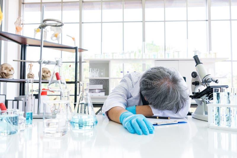睡觉在实验室的被用尽的科学家 人生活方式和职业概念 科学和实验在实验室题材 库存照片