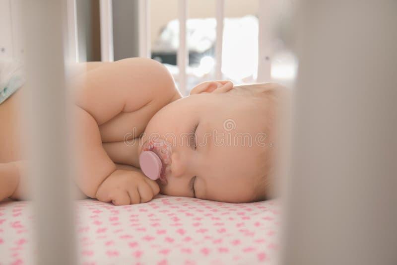 睡觉在小儿床的逗人喜爱的矮小的婴孩 库存图片
