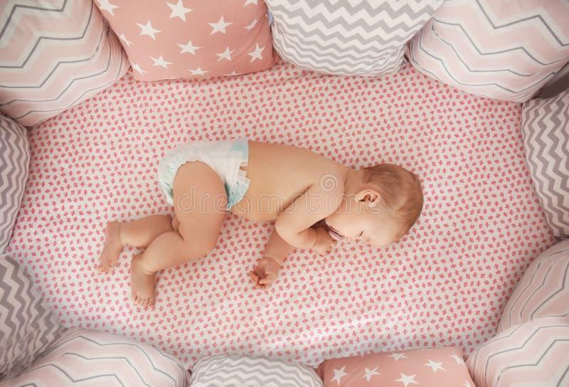 睡觉在小儿床的逗人喜爱的矮小的婴孩 免版税图库摄影
