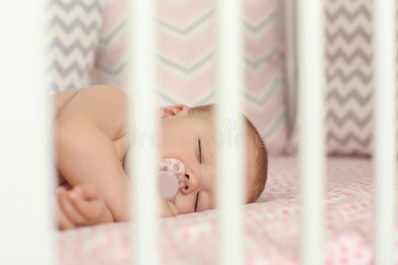 睡觉在小儿床的逗人喜爱的矮小的婴孩 图库摄影