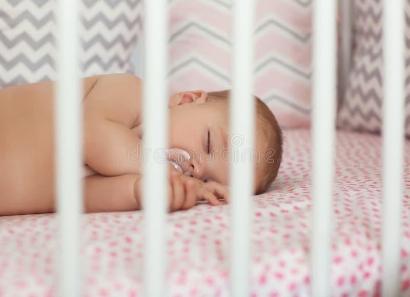 睡觉在小儿床的逗人喜爱的矮小的婴孩 免版税库存图片
