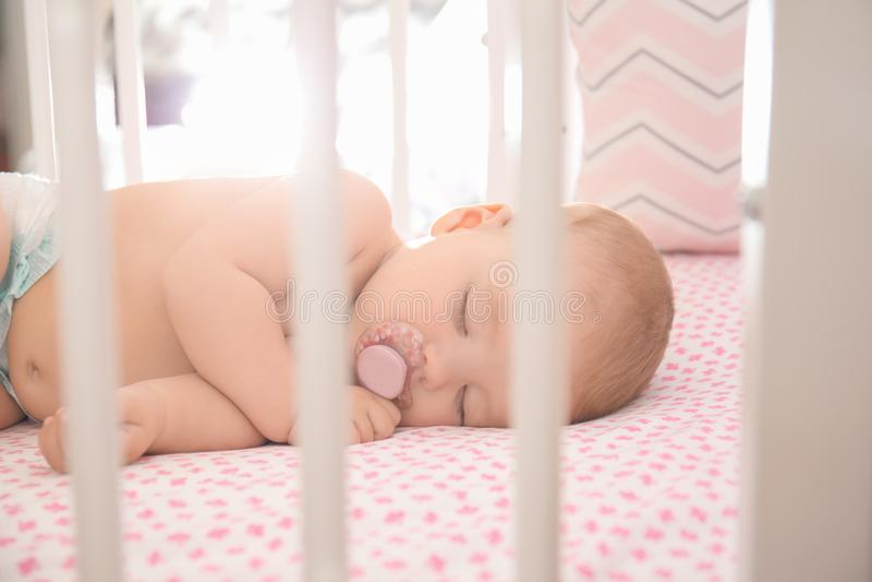 睡觉在小儿床的逗人喜爱的矮小的婴孩 库存照片