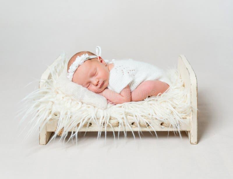 睡觉在小小儿床的愉快的女婴 库存照片
