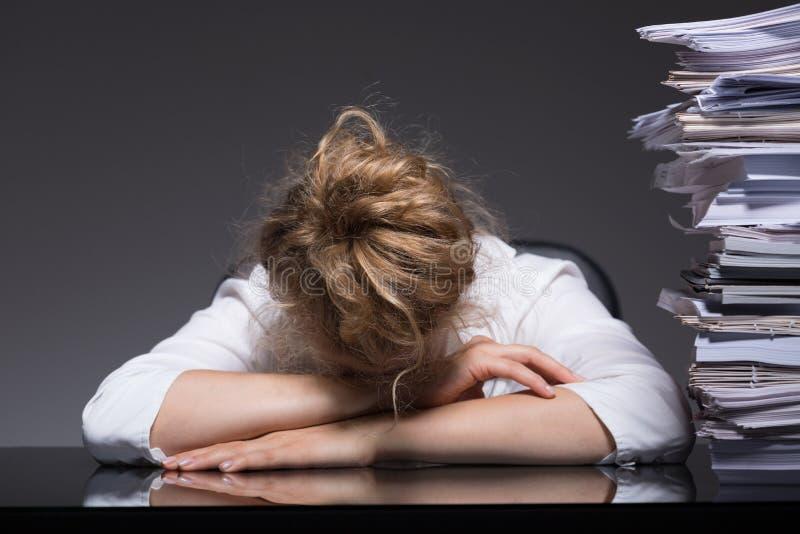 睡觉在工作场所的劳累过度的妇女 免版税库存图片