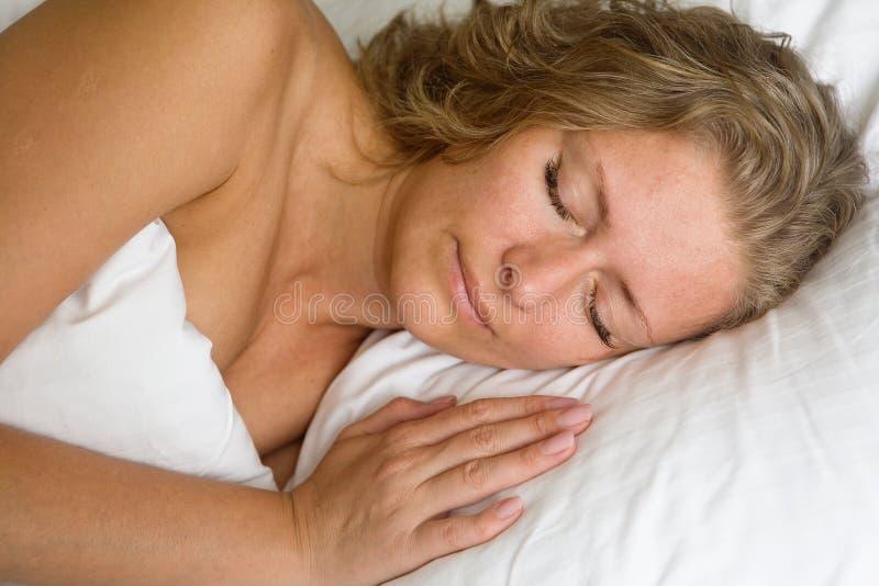 睡觉在床上的俏丽的妇女在盖子下 免版税图库摄影