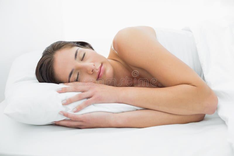 睡觉在床上的俏丽的妇女 免版税库存图片