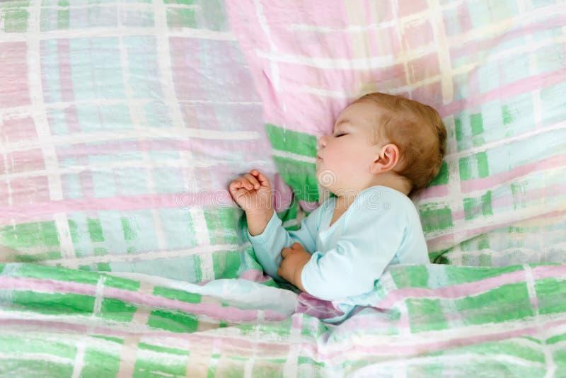 睡觉在床上的可爱的矮小的女婴 作梦在天睡眠期间的镇静平安的孩子 库存图片