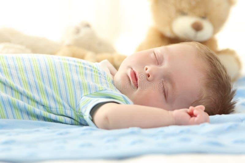 睡觉在床上的唯一婴孩 免版税库存图片