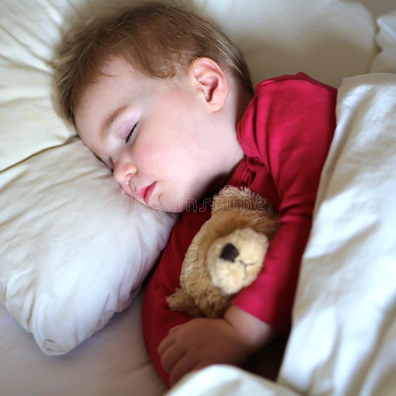 睡觉在床上的小孩 免版税库存照片