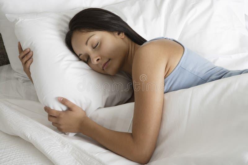 睡觉在床上的少妇 免版税库存照片