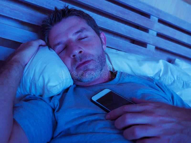 睡觉在床上的年轻互联网上瘾者人在他的手上拿着手机在智能手机和社会媒介网络过度使用的晚上 免版税库存照片