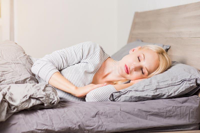 睡觉在床上的年轻女人 库存图片