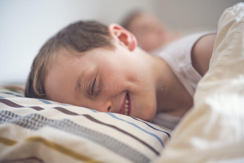 睡觉在床上的年轻男孩 库存照片