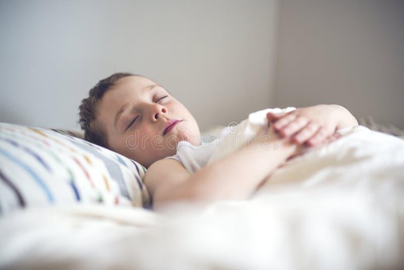 睡觉在床上的年轻男孩 免版税图库摄影