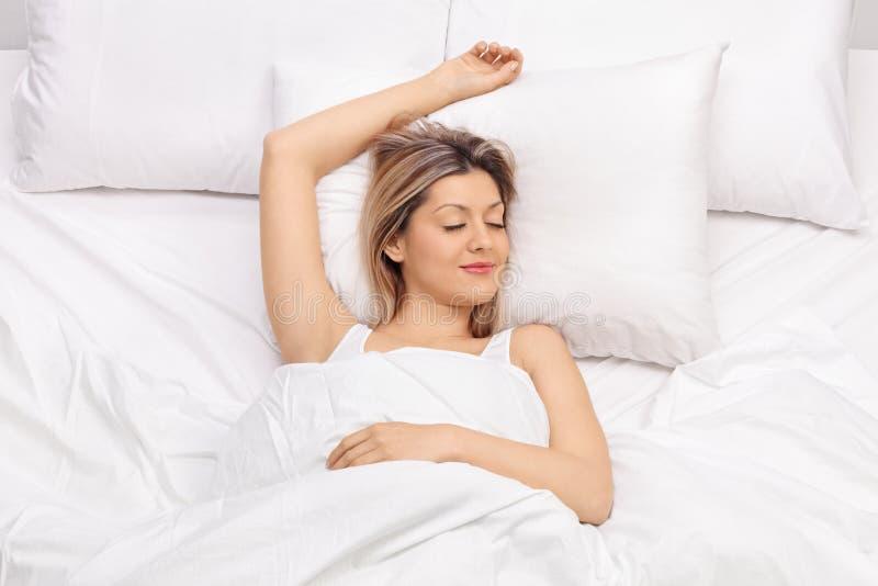 睡觉在床上的快乐的少妇 库存图片