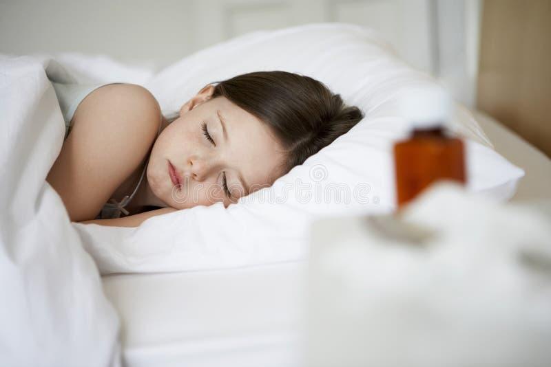 睡觉在床上的病的女孩 免版税库存图片