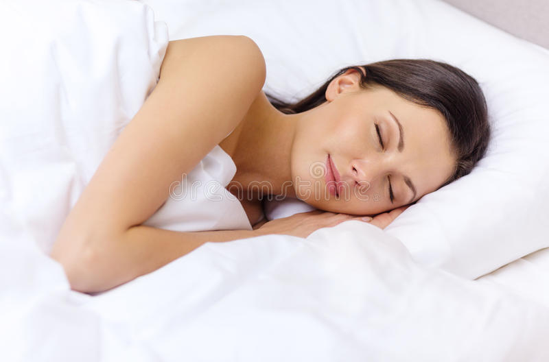 睡觉在床上的美丽的妇女 库存照片