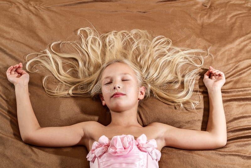 睡觉在床上的美丽的小女孩 免版税库存照片