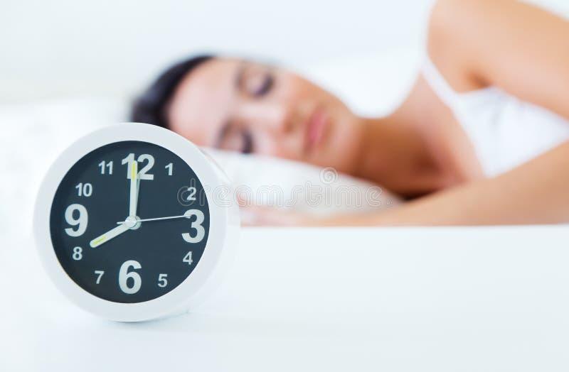 睡觉在床上的美丽的少妇设法醒与丙氨酸 库存图片