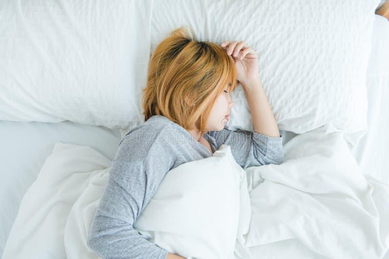 睡觉在床上的美丽的年轻亚裔妇女早晨 有吸引力的亚洲女孩用途上床时间在她舒适的卧室 免版税库存照片
