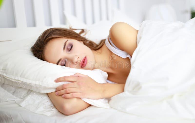 睡觉在床上的美丽的年轻女人早晨 免版税库存图片