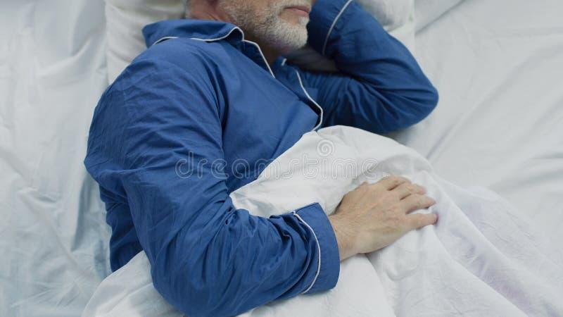 睡觉在床上的老人在早上、恢复时间和健康睡眠 图库摄影