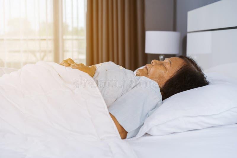 睡觉在床上的老妇人 免版税图库摄影