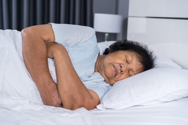 睡觉在床上的老妇人 库存图片