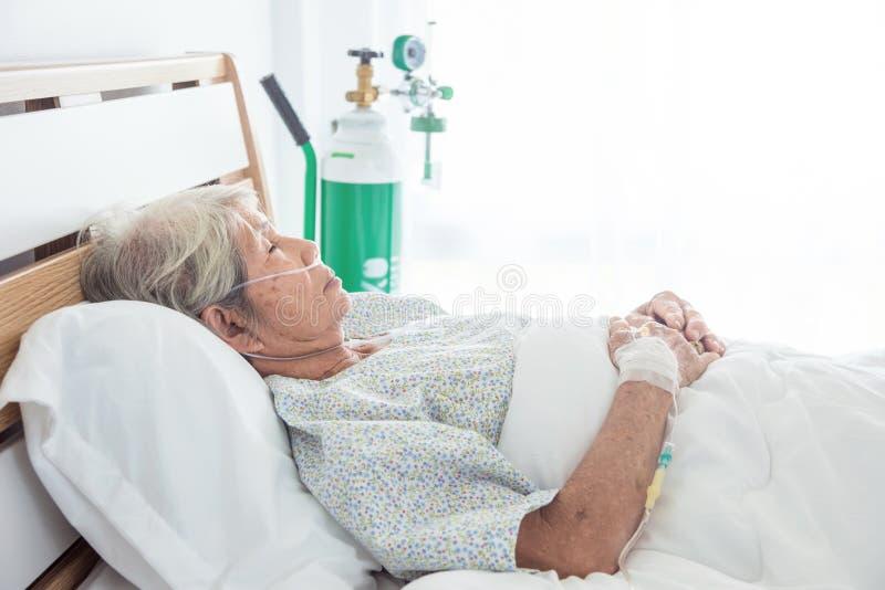 睡觉在床上的资深女性患者在医院 免版税库存照片