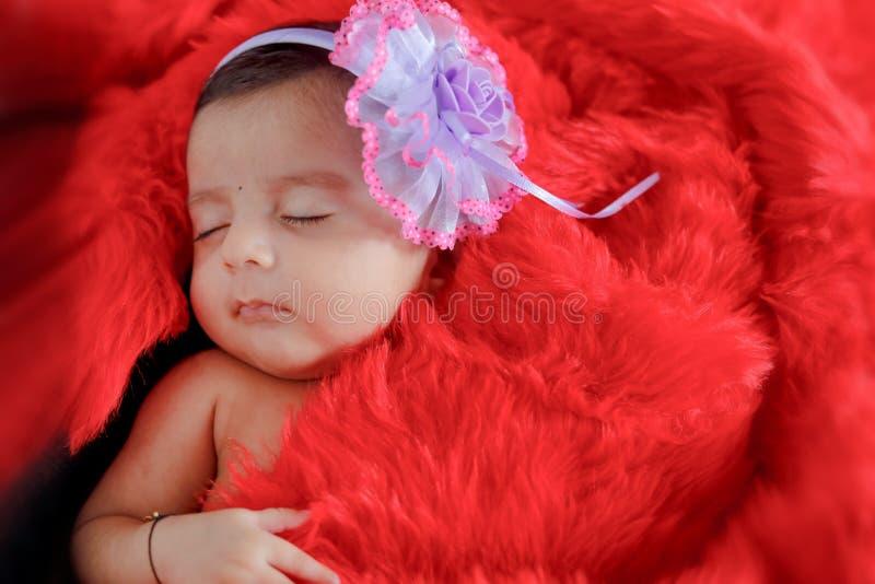 睡觉在床上的逗人喜爱的印地安女婴 免版税库存图片