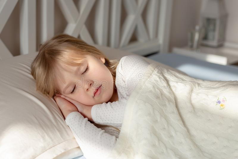 睡觉在床上的逗人喜爱的矮小的白肤金发的小孩女孩 说谎与闭合的眼睛的甜婴孩在太阳下光芒在日出及早 免版税库存照片