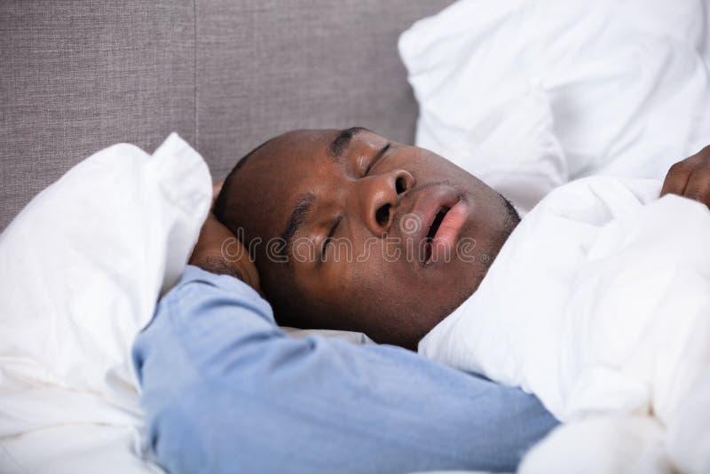 睡觉在床上的非洲人 库存照片