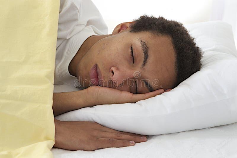 睡觉在床上的非裔美国人的年轻男性 免版税库存照片