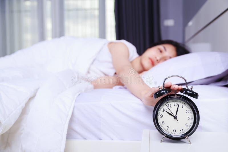 睡觉在床和上升手上的妇女关闭在b的闹钟 库存图片