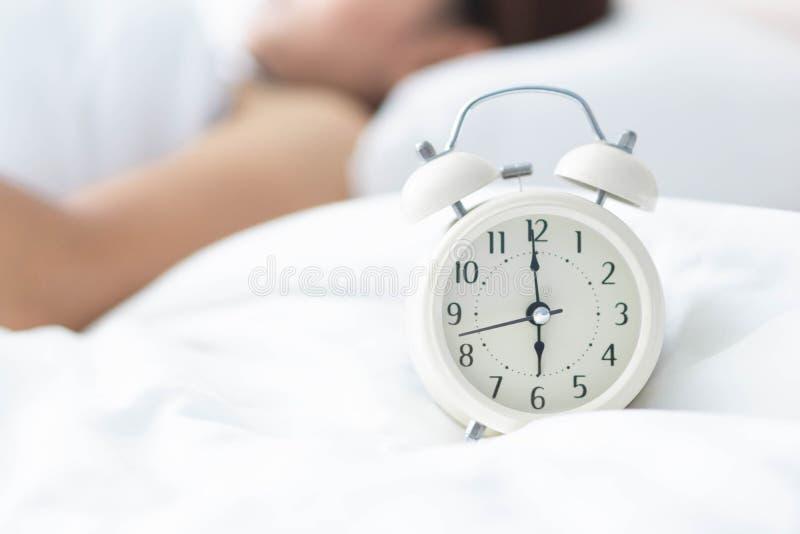 睡觉在床和手在时钟的藏品警报,时刻的特写镜头妇女醒 库存照片