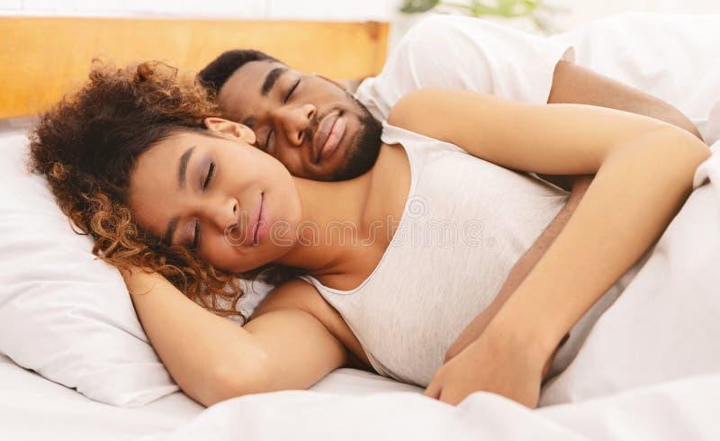 睡觉在床和拥抱上的爱的夫妇 库存照片