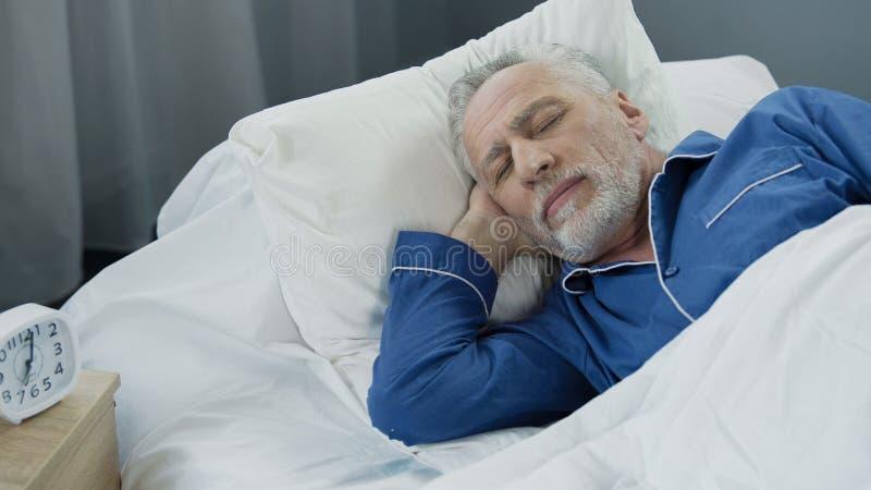 睡觉在床早晨,恢复时间,健康上的退休的人特写镜头  库存图片