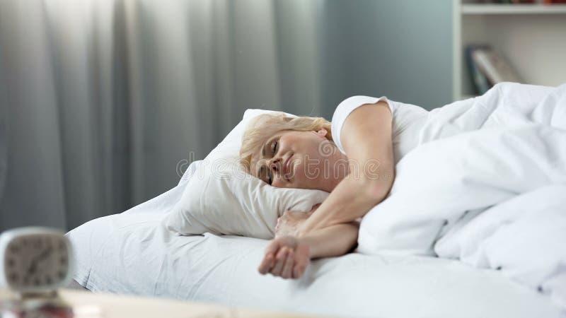 睡觉在床矫形床垫,健康休息,放松的白肤金发的资深妇女 库存照片