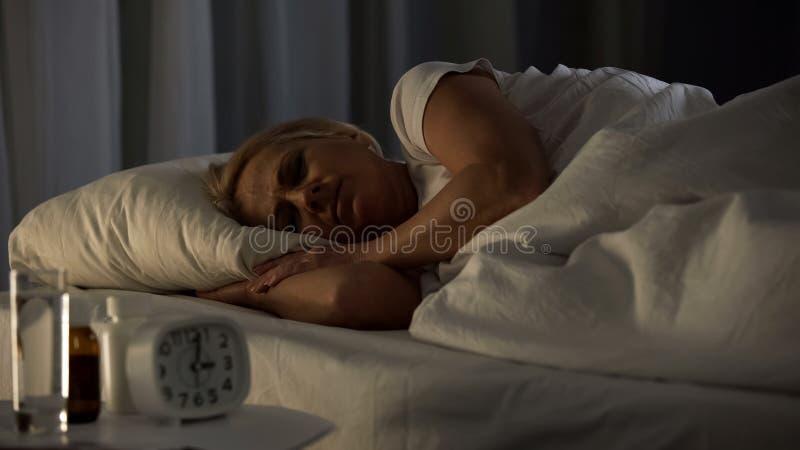睡觉在床,老人院生活方式,领抚恤金者夜休息上的女性领抚恤金者 免版税库存照片