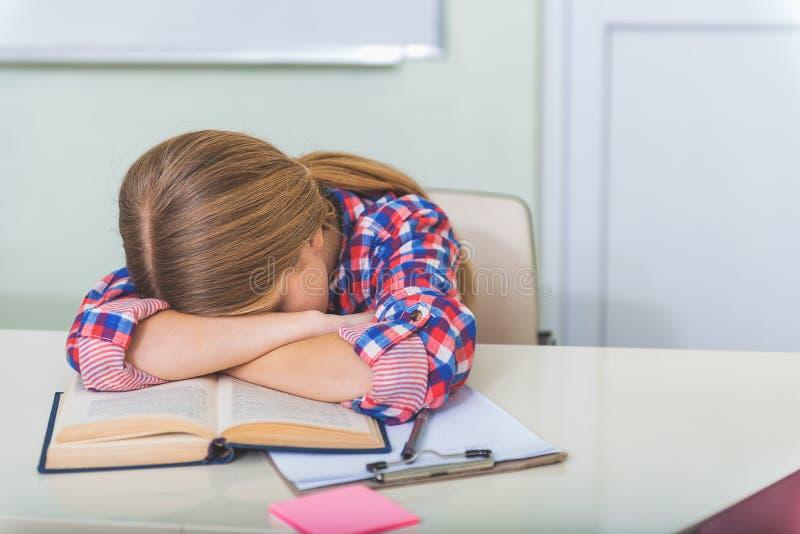 睡觉在教室的疲乏的女孩 免版税库存照片
